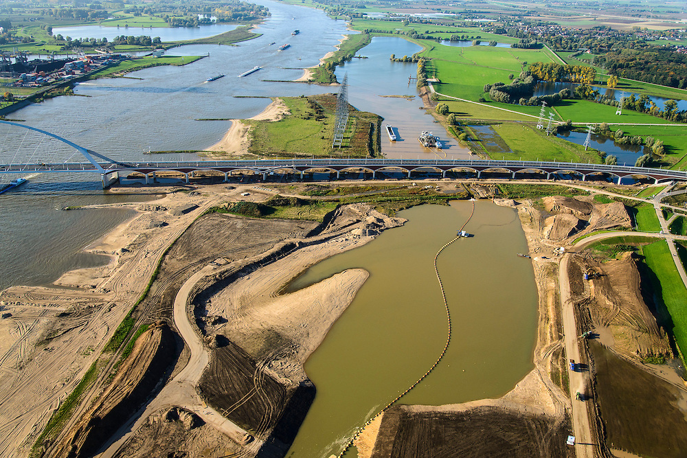 Nederland, Gelderland, Nijmegen, 24-10-2013; <br /> De nieuwe stadsbrug van Nijmegen, De Oversteek.<br /> grondwerkzaamheden voor de dijkteruglegging Lent (Ruimte voor de Rivier). De dijken worden landinwaarts verplaatst en er wordt een nevengeul voor rivier de Waal gegraven. <br /> The new city bridge of Nijmegen on the river Waal, De Oversteek (The Crossing).  Bottom picture the groundworks for the Dike relocation of Lent (project Ruimte voor de Rivier: Room for the River). <br /> luchtfoto (toeslag op standaard tarieven);<br /> aerial photo (additional fee required);<br /> copyright foto/photo Siebe Swart.