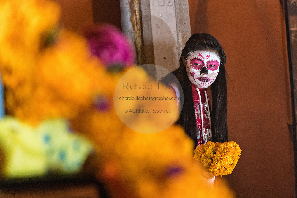 A Mexican girl wearing skeleton face paint views ofrenda altars during the Dead of the Dead festival in San Miguel de Allende, Mexico. The multi-day festival is to remember friends and family members who have died using calaveras, aztec marigolds, alfeniques, papel picado and the favorite foods and beverages of the departed.