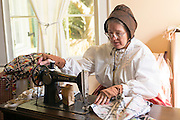 Craftsperson with sewing machine at Vermilionville history museum of Acadian, Creole, Native American cultures, Louisiana, USA