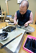 "Teruyoshi Kon decorates a fan handle with lacquer using an implement known as ""shikake-bera"" (""trick spatula"") that is used to make ""kara-nuri"" style Tsugaru lacquerware products in Hirosaki, Japan on 18 Jan. 2013. Photo: Robert Gilhooly.."