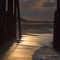 Golden, sunrise light reflects on the wet sand at Frisco Pier, Cape Hatteras National Seashore, NC