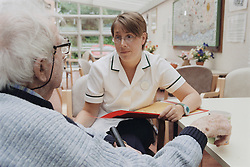 Female occupational therapist talking and listening to elderly man in a wheelchair; making an assessment on progress,