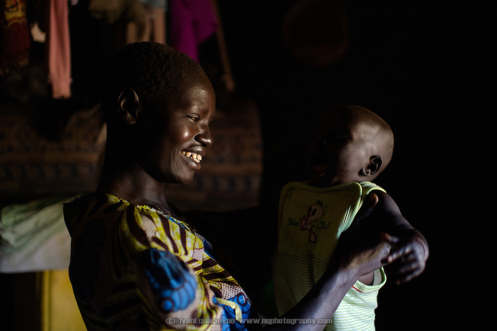 Regina Iyom and her son, James Okwang Okello, at their home in Imurok Payam in Eastern Equatoria, South Sudan on 9 August 2014. Regina's husband is a government soldier, and has been away for about a year. Having come to her current home after having had to flee fighting in Juba in December 2013, she says she receives no support from him—locals say that soldiers frequently go unpaid for long periods of time. Facing acute food insecurity, Regina received seed to plant from Plan International. (On the day she was pictured, Regina was very unwell, with malaria, she said.)