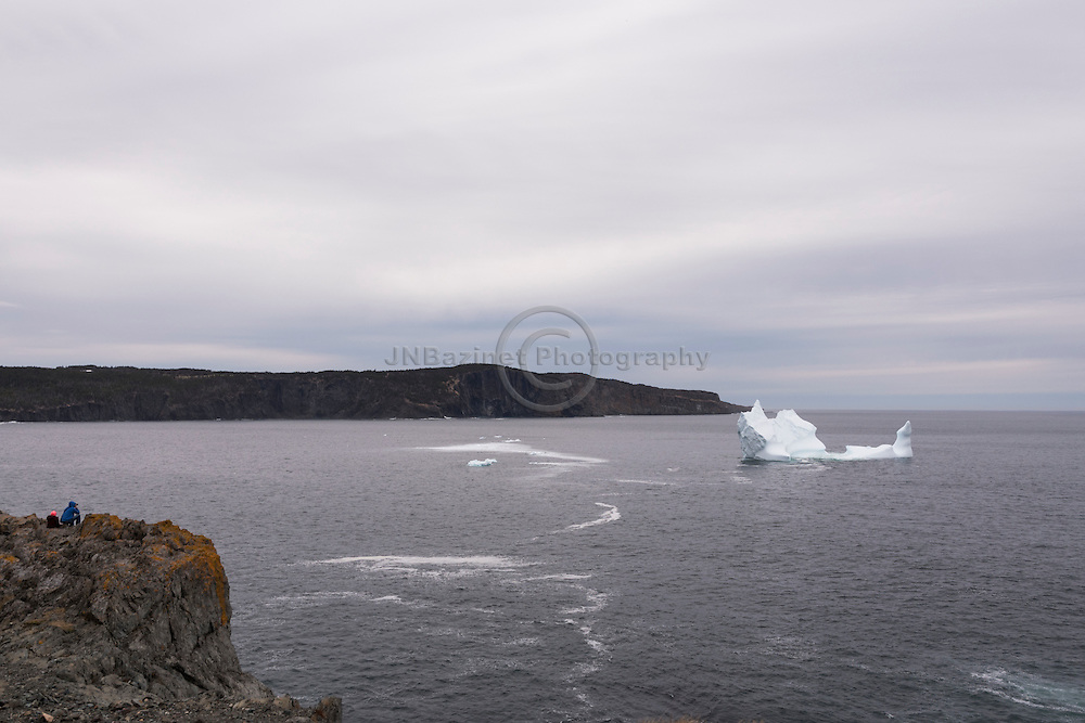 Two people perched on a cliff admiring a beautiful iceberg in Torbay, Newfoundland Canada.