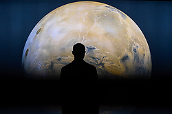 "© Licensed to London News Pictures. 17/10/2019. LONDON, UK. A staff member is seen against a projection of the planet Mars. Preview of ""Moving to Mars"" at the Design Museum. The exhibition explores how sending humans to Mars is a frontier for science as well as design and features over 200 exhibits from NASA, the European Space Agency together with new commissions.  The show is open 18 October to 23 February 2020.  Photo credit: Stephen Chung/LNP"
