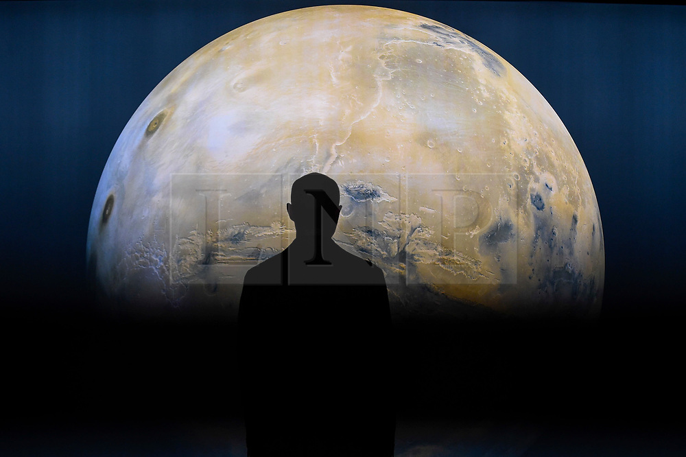 """© Licensed to London News Pictures. 17/10/2019. LONDON, UK. A staff member is seen against a projection of the planet Mars. Preview of """"Moving to Mars"""" at the Design Museum. The exhibition explores how sending humans to Mars is a frontier for science as well as design and features over 200 exhibits from NASA, the European Space Agency together with new commissions.  The show is open 18 October to 23 February 2020.  Photo credit: Stephen Chung/LNP"""
