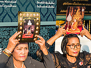 16 DECEMBER 2015 - BANGKOK, THAILAND: Women hold up photos of Somdet Phra Nyanasamvara, Thailand's Supreme Patriarch, during the Patriarch's funeral. He died Oct. 24, 2013. He was ordained as a Buddhist monk in 1933 and appointed as the Supreme Patriarch in 1989. He was the spiritual advisor to Bhumibol Adulyadej, the King of Thailand when the King served as a monk in 1956. Tens of thousands of people lined the streets during the procession to pray for the Patriarch.     PHOTO BY JACK KURTZ