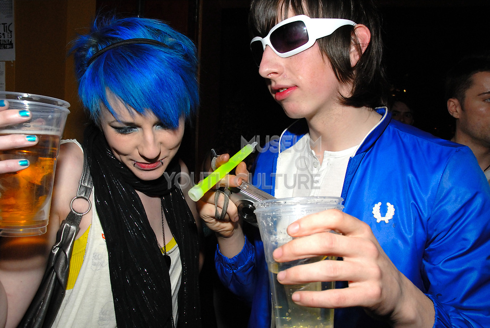 New rave couple, girl with blue hair and boy in electric blue jacket holding a camera and a glowstick, CSS gig, February 2007