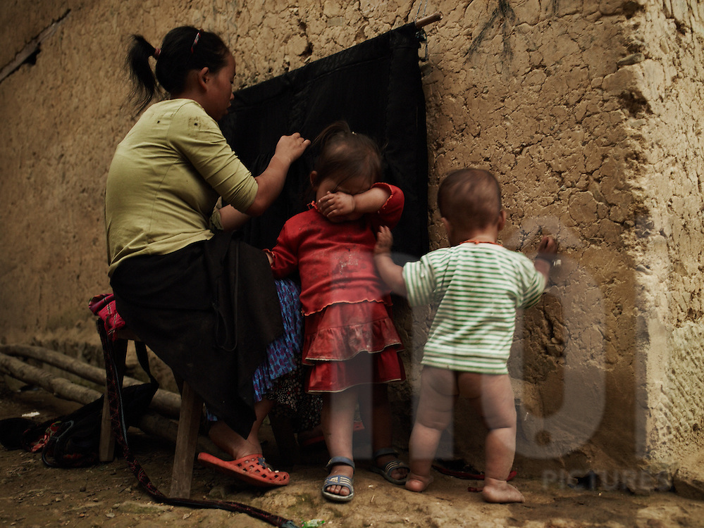 A ethnic woman sews while her kids stand close to her. Her daughter snivels while her son just enjoys life without underwears. Ha Giang province, Vietnam, Asia