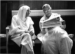 Two elderly women sitting on bench reading newspaper,