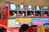 Comuters riding a bus, Bangkok, Thailand