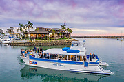 Tourists Cruising With Ocean Adventures in the Dana Point Harbor at Sunset