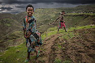 Sister and brother, with a bull whip, on a terraced field in the Ethiopian Highlands as storm clouds build.
