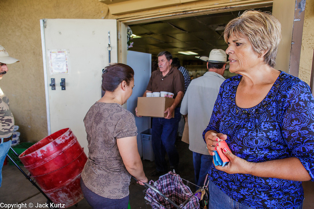 07 AUGUST 2012 - TOLLESON, AZ: BLANCA COREA (right) the Assistant Director at the food bank in Tolleson, AZ, lets clients into the food bank Tuesday. The Tolleson food bank has been operating for more than 20 years. It used to serve mostly the families of migrant farm workers that worked the fields around Tolleson but in the early 2000's many of the farms were sold to real estate developers. Now the food bank serves both farm worker families and people who lost their homes in the real estate crash, that his Phoenix suburbs especially hard. More than 150 families a day are helped by the Tolleson food bank, an increase of more than 50% in the last five years.   PHOTO BY JACK KURTZ