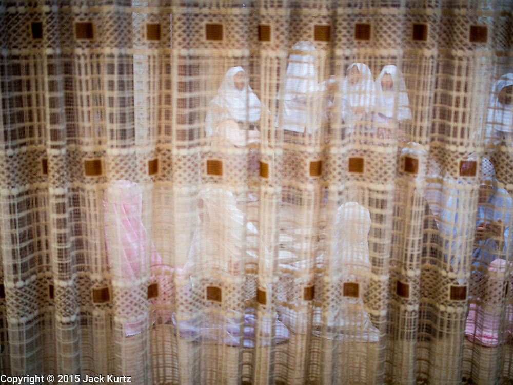 10 APRIL 2015 - BANGKOK, THAILAND: Women in Ton Son Mosque pray from behind a screen during Friday prayers. Masjid Ton Son was the first mosque in Bangkok, founded in 1688 during the reign of King Narai, of the Ayutthaya era. Muslims are about 5 percent of Thailand, but make up a bigger proportion of Bangkok. Thailand's deep south provinces are Muslim majority.    PHOTO BY JACK KURTZ