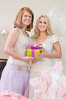 Bride and Friend standing Together holding gift at Bridal Shower