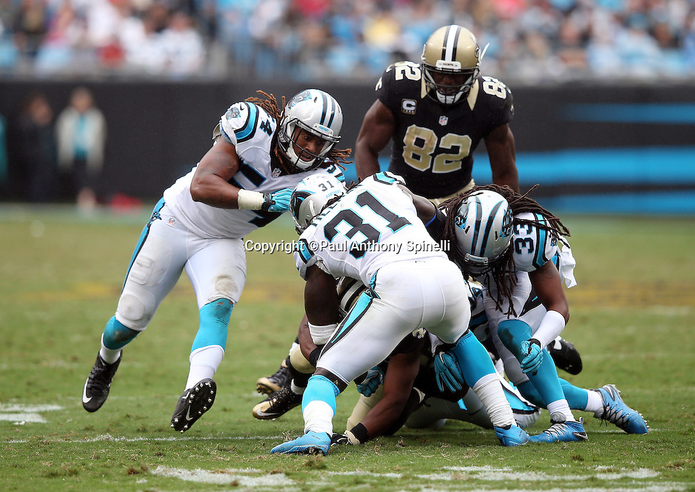 New Orleans Saints running back Mark Ingram (22) gets gang tackled by Carolina Panthers cornerback Charles Tillman (31) and Carolina Panthers free safety Tre Boston (33) during the 2015 NFL week 3 regular season football game against the Carolina Panthers on Sunday, Sept. 27, 2015 in Charlotte, N.C. The Panthers won the game 27-22. (©Paul Anthony Spinelli)