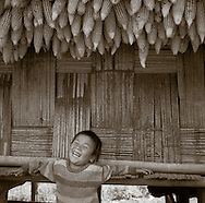 A Liso boy laughs underneath some hanging corn outside his thatched hut, Northern Thailand.