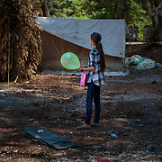 A young refugee from Aleppo, Syria holds her Eid Al Fitr balloon and gift bag distributed by an INGO in Ritsona refugee camp, an hour north of Athens, Greece.<br /> <br /> The Balkan borders were closed to refugees in March 2016. According to the IRC, as of April 2017 62,000 refugees are stranded in Greece, waiting to be relocated to a welcoming country.