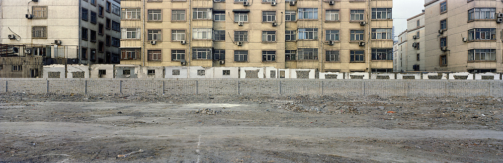 A new wall marks the boundary of a new  construction site. The tattered wall directly behind shows the remains of the old building that once stood and is now destroyed to make way for this new development. The building behind was built in the 1980s. The economic boom in China has meant  that much of the nation's past is consistently erased to make way for the new. Linfen, Shanxi, China. 2010