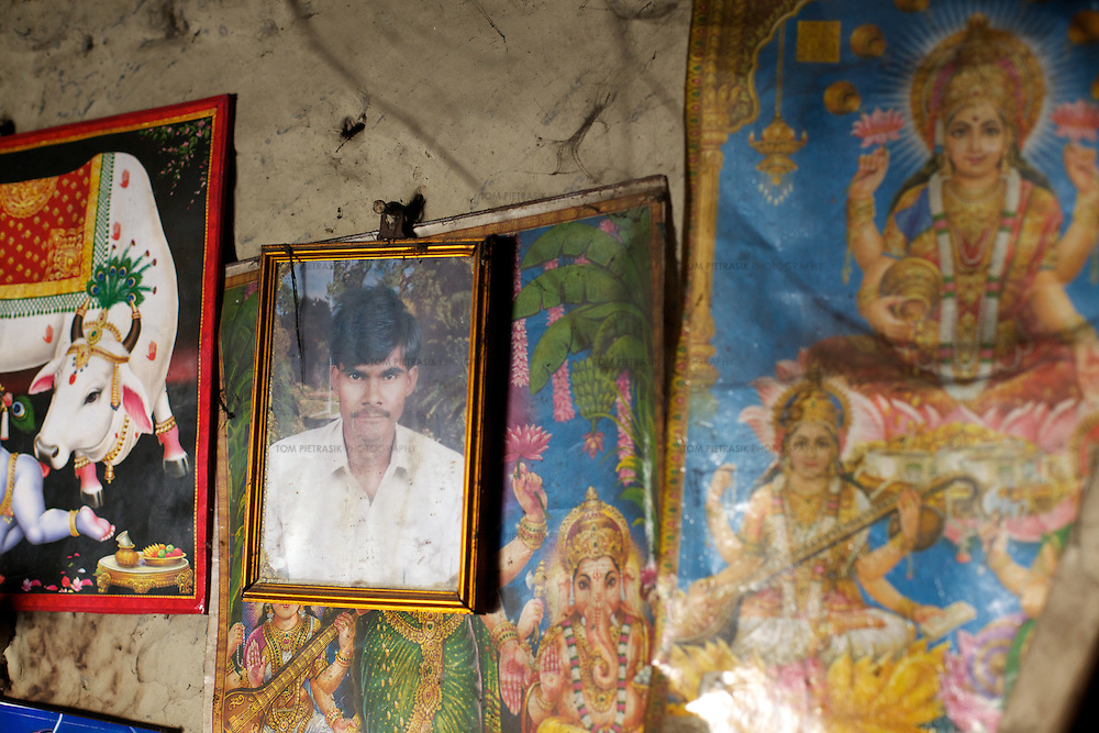 A photo of 22-year old Rajesh hangs on the wall of his family home in the village of Kharihaniya. For many of Kharihaniya's men, a lack of employment oportunity at home, forces them to seek work in far-away cities. Rajesh works as a casual labourer in Mumbai. <br /> <br /> Ostracized, largely illiterate, ignored by an indifferent administration, without land adequate to support their families' needs, the Dalit residents of Kharihaniya village regularly suffer from hunger. The land around the village floods every monsoon season, destroying crops and forcing resident to vacate their homes and move to higher land. Without local opportunities for work, many of Kharihaniya's men have migrated, undertaking menial jobs in far off cities including Mumbai and Chennai. Only about 25% of those living in Kharihaniya village receive subsidized food as part of the PDS (Public Distribution System) even thought the circumstances of most would entitle them to such assistance. Intervention by Oxfam partners (Grameen Development Services) led to the establishing of a local SHG (Self Help Group) three years ago. The SHG allows women to save and borrow and invest in their farms while offering an opportunity to discuss problems and share ideas. <br /> <br /> Photo: Tom Pietrasik<br /> Kharihaniya, Marajganj District, Uttar Pradesh. India<br /> February 27th 2011