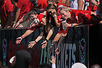 Students reach for high-fives from Wolfpack marching band members prior to the start of the game.