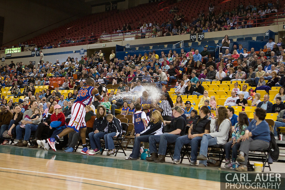 April 30th, 2010 - Anchorage, Alaska:  It is time for a water break as Globetrotter Hi-Lite Bruton shares a bucket of watter with teammate Moo Moo Evans, the ref, and a group of fans.