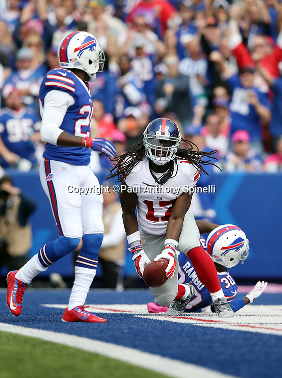 New York Giants wide receiver Dwayne Harris (17) starts to celebrate after catching a 21 yard touchdown catch and run good for a 9-3 first quarter Giants lead during the 2015 NFL week 4 regular season football game against the Buffalo Bills on Sunday, Oct. 4, 2015 in Orchard Park, N.Y. The Giants won the game 24-10. (©Paul Anthony Spinelli)
