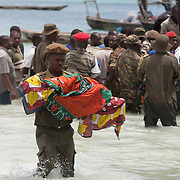 The bodies of children are carried to shore following the ferry accident off the coast of Zanzibar.