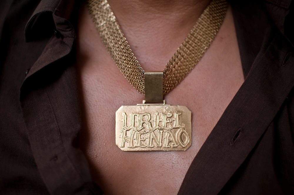 Narco-ballads singer, Uriel Henao's gold necklace. Henao's wardrobe for concerts includes leather pants and jacket, snakeskin boots and belt, a cowboy hat, and a lot of gold jewelry.