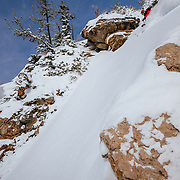 Kim Havell skis a steep powder line in the Teton backcountry during a sunny day.