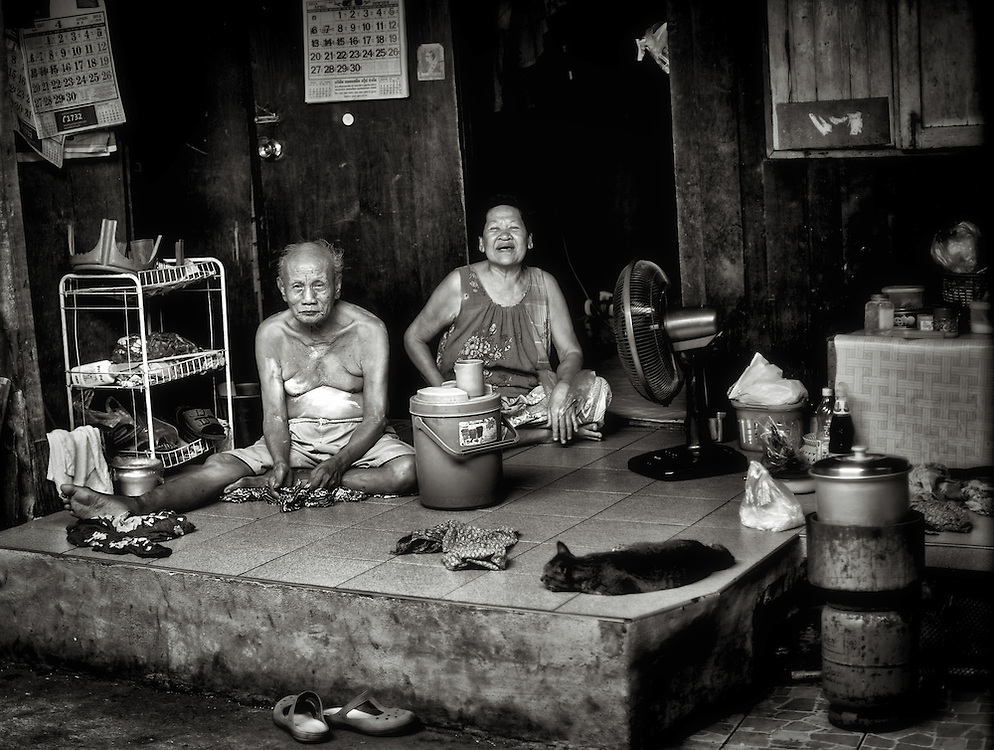 A couple cooling off on their front porch in the Khlong Toei district of Bangkok, Thailand.