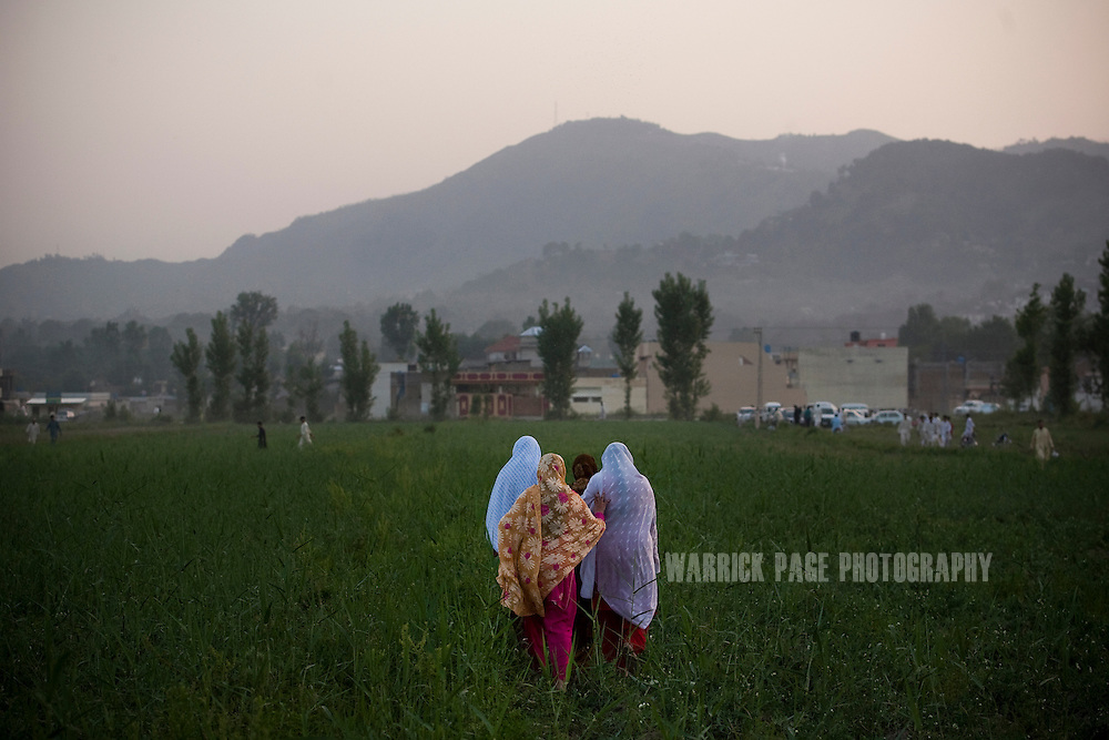 Pakistani women walk through a field outside the compound where Osama Bin Laden was killed in an operation by US Navy Seals, on May 3, 2011, in Abottabad, Pakistan.  The operation, code-named Operation Neptune Spear, was launched from neighbouring Afghanistan by Seal Team Six. U.S. forces took bin Laden's body to Afghanistan for identification, then dumped it the Arabian Sea. Pakistan has since been widely suspected as having prior knowledge of his whereabouts as the compound was less than a kilometre from the country's biggest military academy. Osama bin Laden was allegedly responsible for supporting the bombing of the US Embassy in Nairobi, Kenya, the attack on the USS Cole and the suicidal attacks of September 11, 2001 in the US. (Photo by Warrick Page)