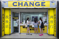 Three young female mainland Chinese tourists at currency exchange shop in Hong Kong
