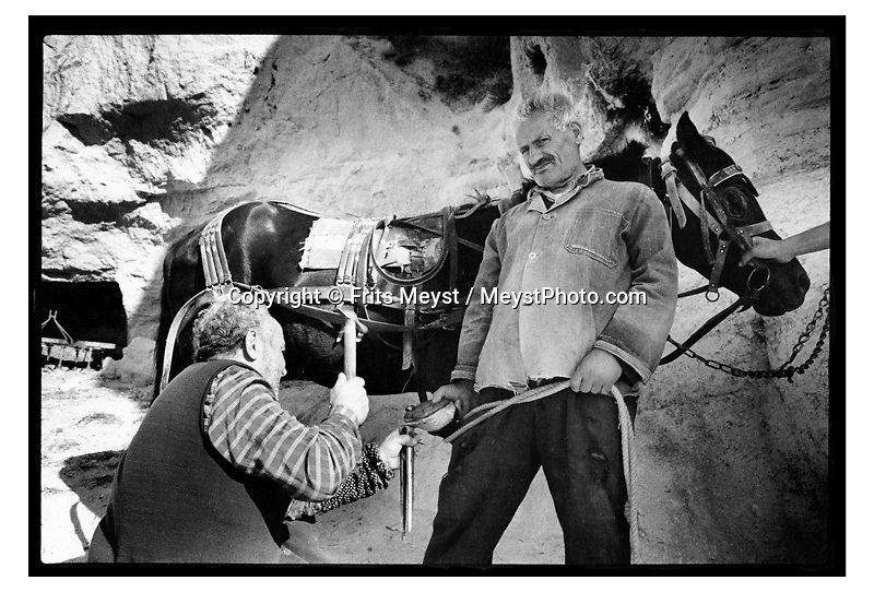 GOREME, CAPPADOCIA, TURKEY, 2000. A smith puts new irons underneath the hoofs of a mule. Traditional life in Cappadocia has come under heavy strain, due to the increased tourism. the young generation is not interested in working the fields if they can work in a carpetshop, restaurant or bar. Therefore centuries old skills and habits will die with the elderly. Cappadocia is knowns for its landscape with conical shaped rock formations and cave dwellings in which the local people live. ©Photo by Frits Meyst/Adventure4ever.com