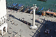 tourists taking cover from the heat in the shadow of the winged Lion of St Marks tower statue Venice Italy
