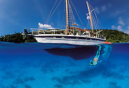 Underwater split level view of ketch in clear blue water anchorage in Vava'u, with snorkeller. Tonga. South Pacific