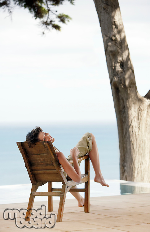 Woman sitting on lounge chair by infinity pool overlooking sea
