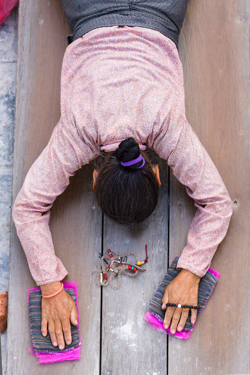 Buddhist woman prostrating herself at Bodnath stupa early in the morning. Kathmandu, Nepal.<br /> <br /> Licensed by Tandem Stills + Motion (2013). Available here: https://tandemstock.com/assets/50909170