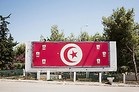 TUNIS, TUNISIA - 26 JULY 2013: A giant Tunisian flag covers a billboard, together with photos of martyrs of the revolution, in the Ettadhamen district in Tunis, Tunisia, on July 26th 2013.<br /> <br /> Tunisia, birthplace of the Arab Spring revolutionary movement, was plunged into a new political crisis on Thursday when assassins shot Mohamed Brahmi, 58, leader of the Arab nationalist People's Party, an opposition party leader outside his home in a hail of gunfire.
