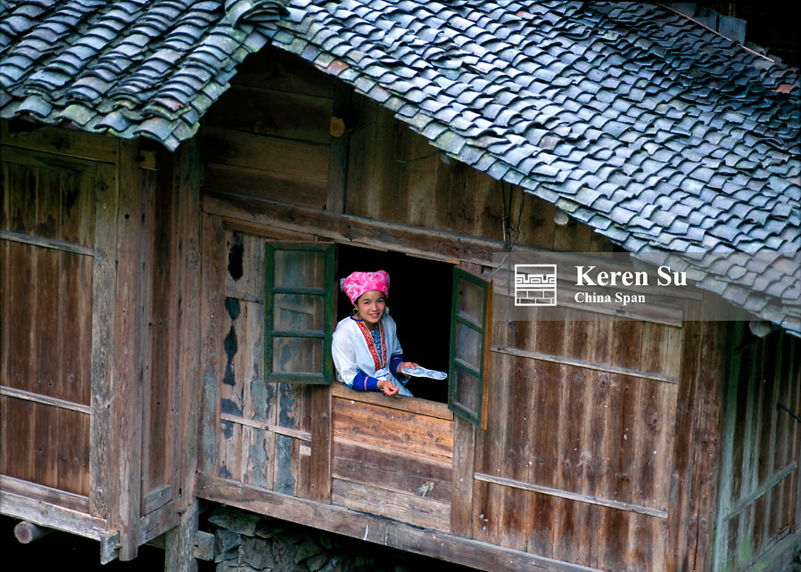 Zhuang girl by the window of traditional wood house in the village, Longsheng, Guangxi Province, China