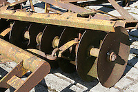 Rusty farm plough machinery in a farmyard in Ireland