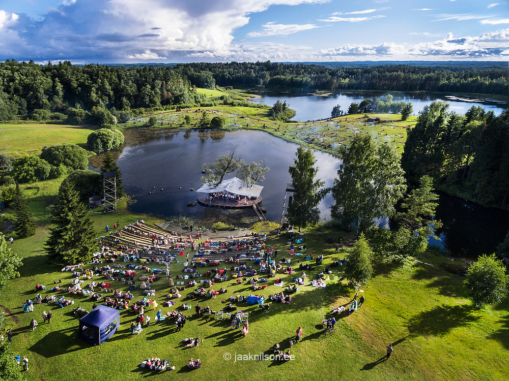 Leigo lake music festival in Estonia. Aerial view, people, water. Open-air concert arena, stage.