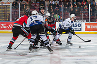 KELOWNA, BC - NOVEMBER 20: Referee Matt Hicketts looks for an exiit from the face-off scrum after dropping the puckk between Alex Swetlikoff #17 of the Kelowna Rockets and Kaid Oliver #34 of the Victoria Royals  at Prospera Place on November 20, 2019 in Kelowna, Canada. (Photo by Marissa Baecker/Shoot the Breeze)