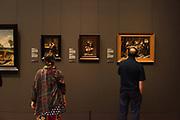 Bezoekers van het Rijksmuseum kijken naar 17 eeuwse schilderijen uit de Gouden Eeuw collectie van het Rijksmuseum.