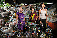 Ibu Roseliana (l) at the recycling business owned by her parents just outside the Jongaya leprosy settlement, Makassar, Sulawesi, Indonesia. Ibu Roseliana, 43, was born in Jongaya.  She does not have leprosy, nor do her 3 children and 2 grandchildren, but her parents, Sehu Daeng Pali and Fatimah, both have the disease.  Sehu Daeng Pali moved to Jongaya in the '60's looking for medical treatment and shortly after met and married his wife in the settlement.  They set up a recycling business just outside Jongaya in 1982 where Ibu Roseliana now works.  The business now employs people who have been infected with leprosy and those that are free from the disease.