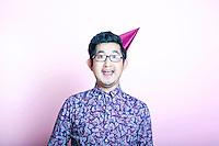 Young Geeky Asian Man wearing party hat
