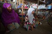 "Sept. 28, 2009 -- TANJONG DATO, THAILAND: Women pray during a religious ceremony in their home in the Muslim village of Tanjong Dato, in the province of Pattani, Thailand. Everybody in the village is Muslim and they say they have no problems, but the roads around the village leading to the provincial capital of Pattani are too dangerous for them to use once it gets dark. Thailand's three southern most provinces; Yala, Pattani and Narathiwat are often called ""restive"" and a decades long Muslim insurgency has gained traction recently. Nearly 4,000 people have been killed since 2004. The three southern provinces are under emergency control and there are more than 60,000 Thai military, police and paramilitary militia forces trying to keep the peace battling insurgents who favor car bombs and assassination.   Photo by Jack Kurtz / ZUMA Press"