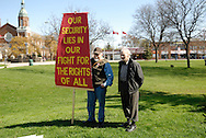 Windsor, Canada. 01 May 2015. -- A G Smith, an artist, holds a sign and talks with a friend  just before the start of the Festival of Bread and Roses.-- MayWorks Windsor 2015, a festival for workers and social justice art opens on May Day, International Workers's Day, with a Bread and Roses festival, Detournements exhibition opening and a Windsor Feminist Theatre fundraiser.