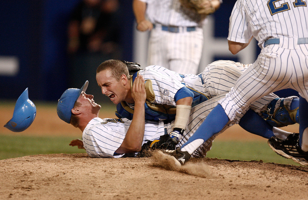 UCLA closing pitcher David Berg, left, is tackled by catcher Shane Zeile after the final out of their NCAA college baseball tournament super regional game against Cal State Fullerton, Saturday, June 8, 2013, in Fullerton, Calif. UCLA won 3-0 to advance to the College World Series. (AP Photo/Jason Redmond)